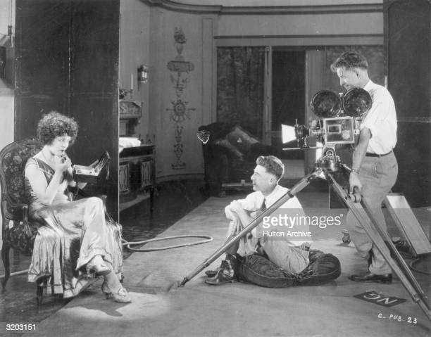 Canadian actor Marie Prevost applies lipstick as American film director William Beaudine and American cameraman Ray June watch and wait on the set of...