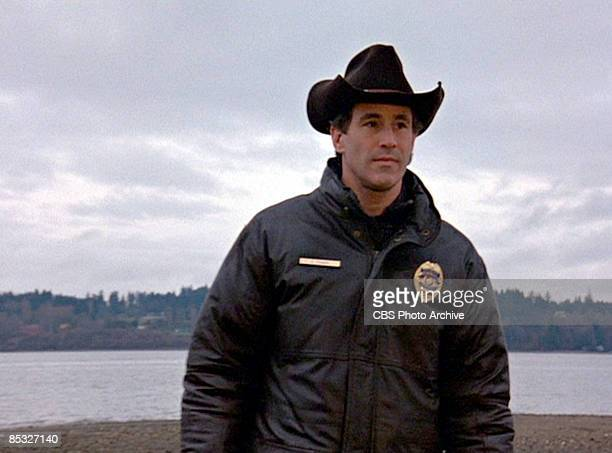 Canadian actor Michael Ontkean stands on a rocky beach in a scene from the pilot episode of the television series 'Twin Peaks' originally broadcast...