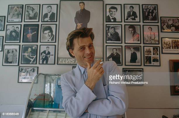 Canadian actor Nicholas Campbell smoking a cigarette at home He is standing against a jukebox in front of a wall of old photographs of Elvis Presley...