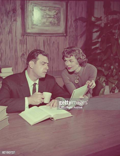 Canadian actor Raymond Burr and American actress Barbara Hale discuss a document in a scene from the television series 'Perry Mason' 1959