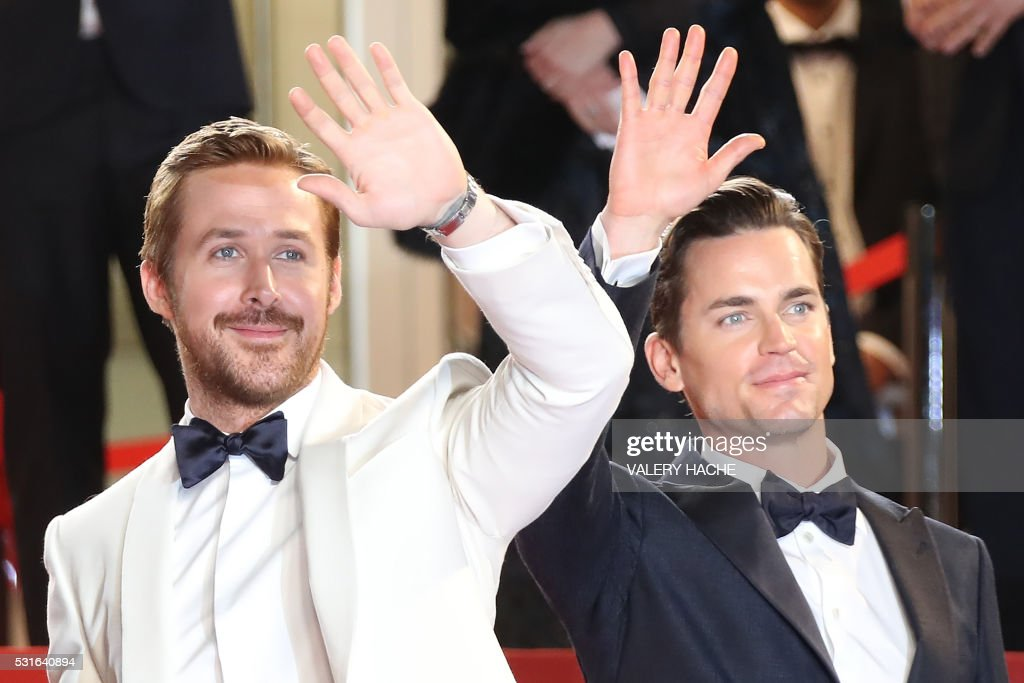 TOPSHOT - Canadian actor Ryan Gosling (L) and US actor Matt Bomer wave as they arrive on May 15, 2016 for the screening of the film 'The Nice Guys' at the 69th Cannes Film Festival in Cannes, southern France. / AFP PHOTO / Valery HACHE