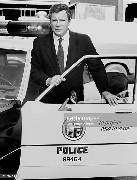 Canadian actor singer and author William Shatner stands behind the door of a police car as he hosts the CBS Television true crime program 'Rescue...