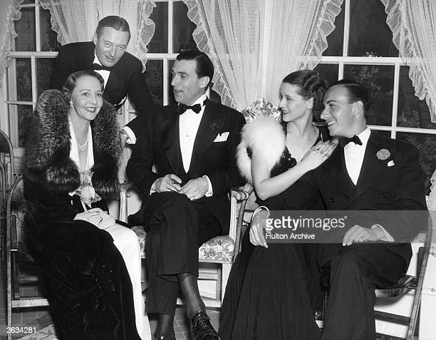 Canadian actor Walter Pidgeon centre attends a dinner party at the home of Raul Walsh the other guests with him are from left to right Rita Kauffman...