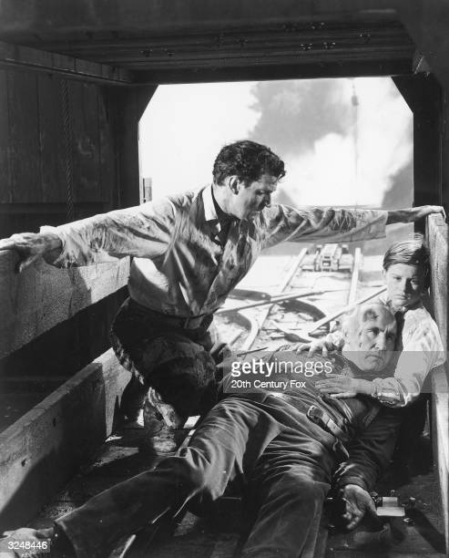 Canadian actor Walter Pidgeon kneels over Scottish born actor Donald Crisp and British actor Roddy McDowall inside a railway freight car in a still...
