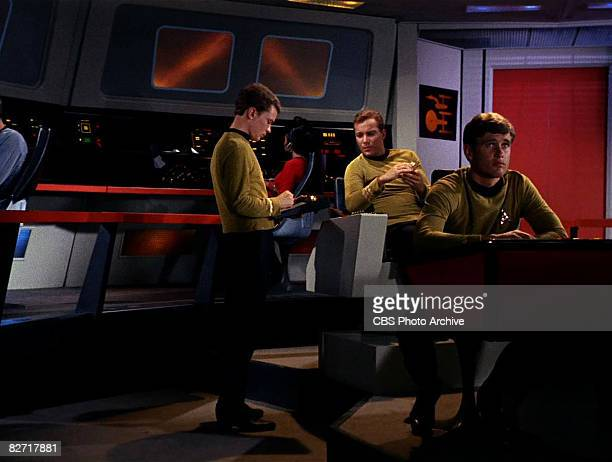 Canadian actor William Shatner sits on the bridge of the USS Enterprise and speaks with an unidentified actor while a second unidentified actor sits...