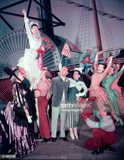 Canadian actress Allyn McLerie raises her arm while others including American actors Eddie Albert and Mary McCarty watch in a scene from the Broadway...