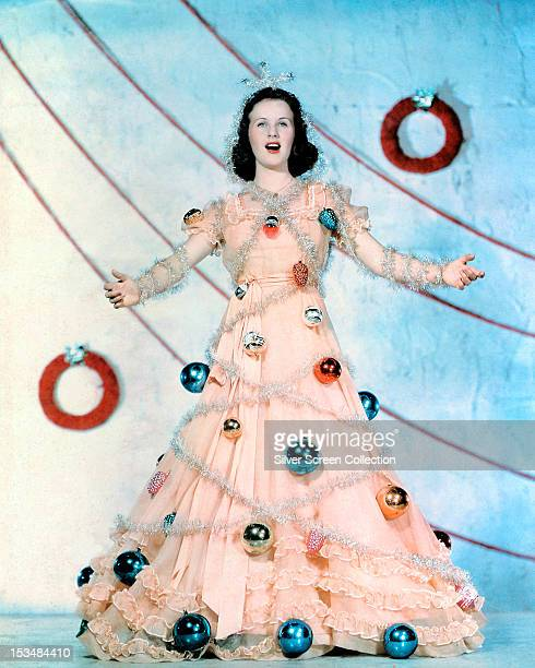 Canadian actress Deanna Durbin as a Christmas tree fairy in a peachcoloured dress decorated with baubles and tinsel circa 1945