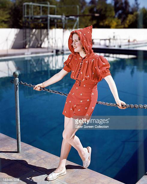 Canadian actress Deanna Durbin by a swimming pool in a red hooded top and matching shorts circa 1940
