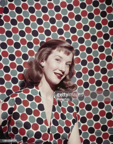 Canadian actress Lois Maxwell posed wearing a polka dot dress against a matching polka dot background in July 1952