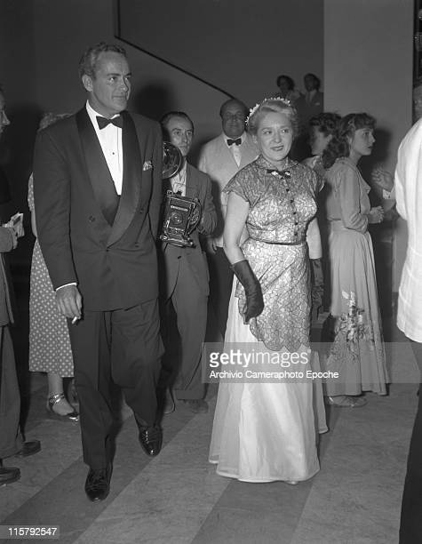 Canadian actress Mary Pickford wearing a lace evening dress her husband Charles Rogers smoking a cigarette next to her while entering the Movie...