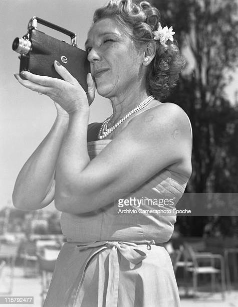 Canadian actress Mary Pickford wearing a strapless dress a pearl necklace and flower in her hair shooting with a cinecamera Venice August 1948