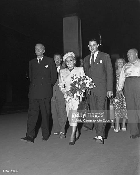 Canadian actress Mary Pickford wearing a tailleur a hat with veil holding a handbag and a posy walking surrounded by people Venice August 1948