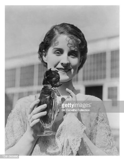 Canadian Actress Norma Shearer holding a glass with one of the smallest dogs of the world in it in a candid shot taken at the MGM lot United States.
