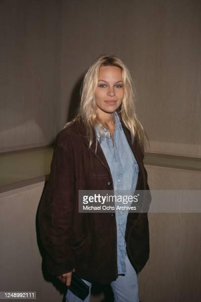 Canadian actress Pamela Anderson, wearing a dark brown jacket over a denim shirt, circa 1992.
