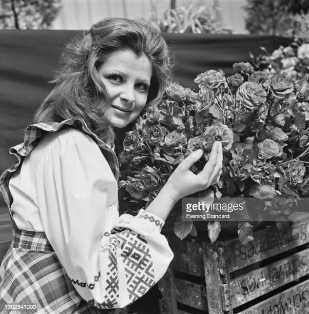 Canadian actress Rita Merkelis with a crate of roses, UK, 28th July 1972.