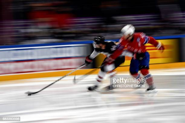 A Canadian and a Norwegian player vie during the IIHF Men's World Championship group B ice hockey match between Canada and Norway on May 15 2017 in...