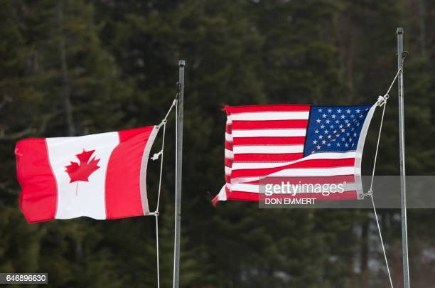 Canadian and American flags are seen at the US/Canada border March 1 in Pittsburg New Hampshire / AFP PHOTO / Don EMMERT