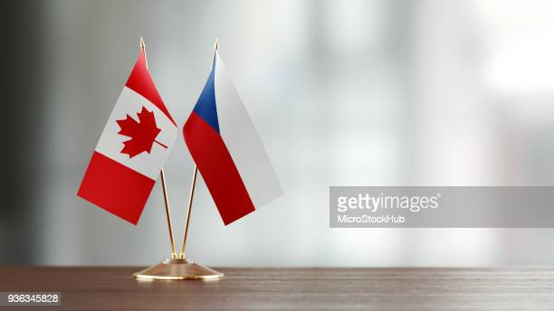 canadian and czechoslovakian flag pair on a desk over defocused background - diplomacy stock pictures, royalty-free photos & images