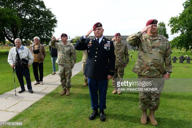 US Canadian and German soldiers salute during a ceremony at the German war cemetery in La Cambe Normandy northwestern France on June 5 as part of...