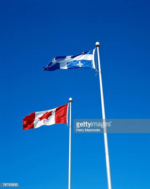 Canadian and Quebec flags with clear blue sky, Canada