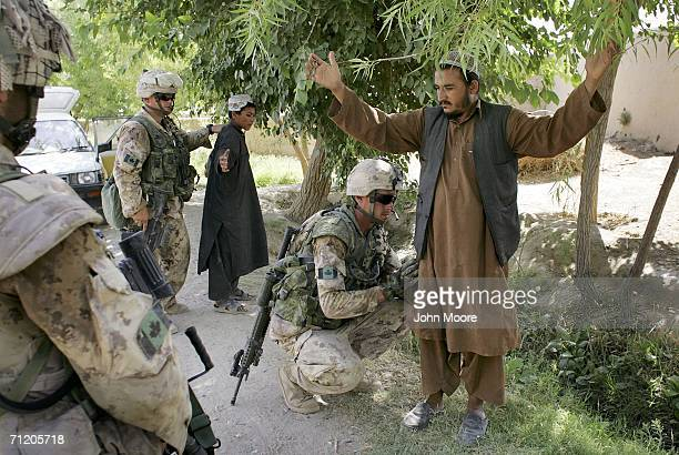 Canadian army soldiers search Afghan civilians at a checkpoint June 14, 2006 in Panjwai, 30 kilometers southwest of Kandahar, Afghanistan. The...