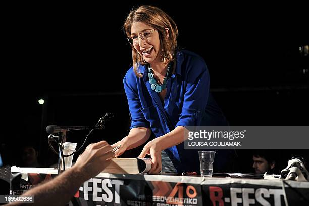 Canadian author and social activist Naomi Klein signs a copy of her book after addressing the Athens antiauthoriterian festival late on May 25 2013...