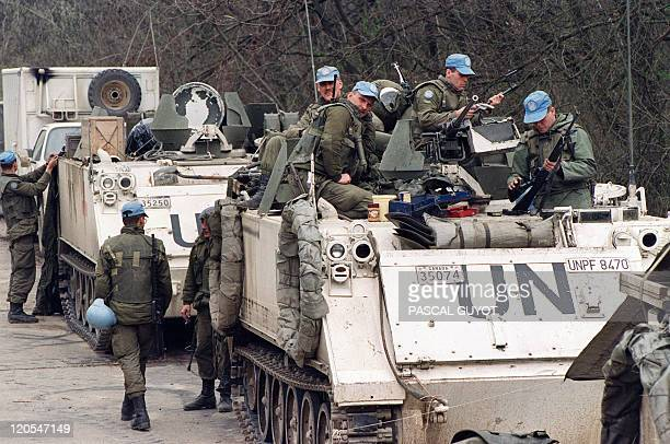 Canadian blue helmets check their weapons 17 April 1993 near Tuzla's airport waiting to depart for the Moslem enclave of Srebrenica where some 30000...