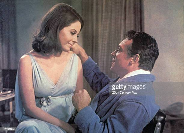 Canadian born actor Barbara Parkins, wearing a nightgown, sits in American actor Paul Burke's lap in a still from the film, 'Valley of the Dolls,'...