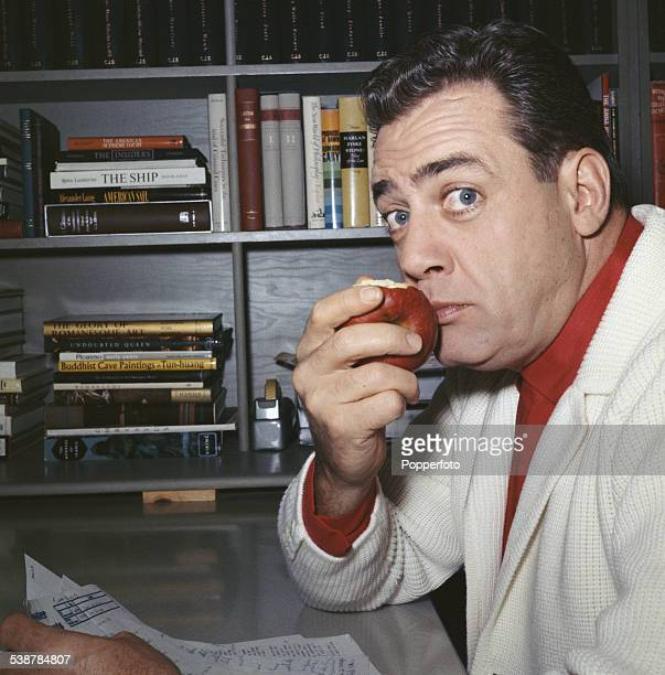 Canadian born actor Raymond Burr who plays the title role in the television drama series Perry Mason pictured eating an apple in a library in 1962