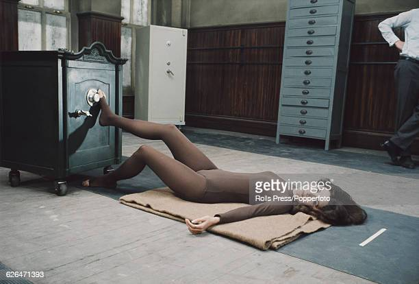 Canadian born American actress Barbara Parkins, dressed in a brown leotard and tights as the character BA, attempts to open a safe with her foot...