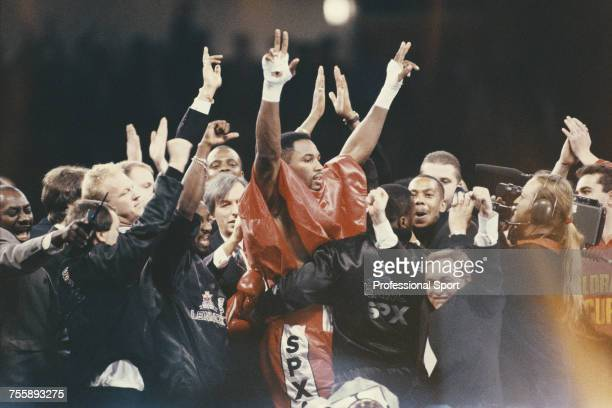 Canadian born British heavyweight boxer Lennox Lewis celebrates with members of this entourage and corner team including manager Frank Maloney after...