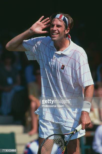 Canadian born British tennis player Greg Rusedski, wearing a union flag headband, listens for a line judge call during competition to reach the...