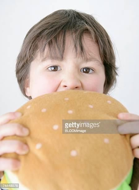Canadian boy eating hamburger of toy