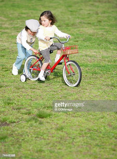 Canadian boy helping girl riding on bicycle on meadow