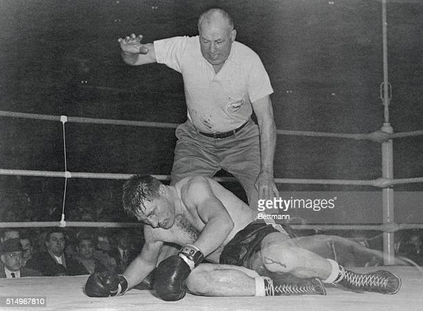 Canadian challenger Yvon Durelle lies dazed on the mat in the 11th round championship bout at Montreal Forum here as referee Jack Sharkey begins the...