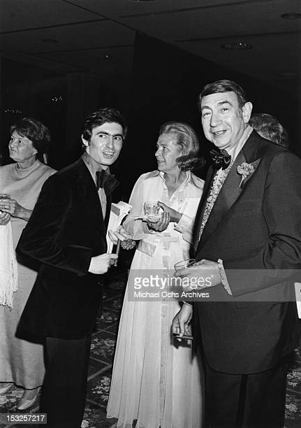 Canadian comedian actor writer director and author David Steinberg chats with sportscaster Howard Cosell and wife Emmy Cosell at an event circa 1975...