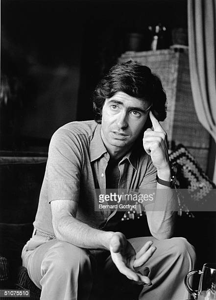 Canadian comedian and director David Steinberg sits on a couch gesturing with on hand and pressing a finger to his head with the other 1974