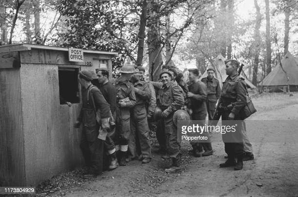 Canadian Corps infantry soldiers line up to receive letters and mail at a temporary post office at a Canadian Army camp in England during World War...