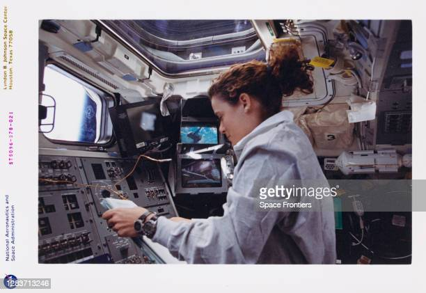 Canadian CSA astronaut Julie Payette operates the Canadian-built Remote Manipulator System from the aft flight deck, with monitors providing Payette...