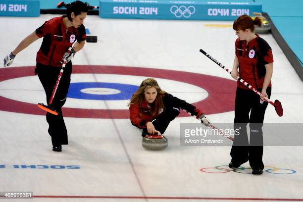 Canadian curler Jennifer Jones throws the stone as sweepers Jill Officer and Dawn McEwen look on during a women's curling qualifier against Great...