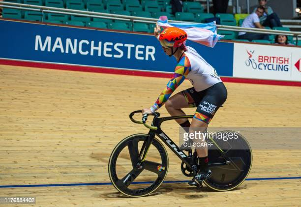 Canadian cyclist Rachel McKinnon carries a Transgender Pride flag as she celebrates winning the F3539 Sprint Final during the 2019 UCI Track Cycling...