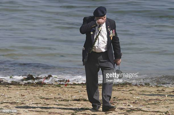 Canadian D-Day veteran wipes his eyes while visiting the beach where he and other Candian soldiers landed 60 years ago June 6, 2004 at Juno Beach in...