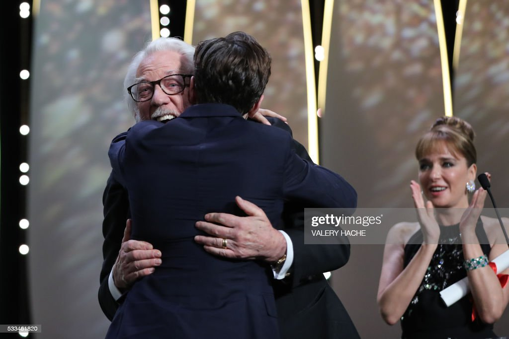 Canadian director Xavier Dolan (L) hugs Canadian actor and member of the Jury Donald Sutherland after being awarded with the Grand Prix for the film 'It's Only The End Of The World (Juste La Fin Du Monde)' during the closing ceremony of the 69th Cannes Film Festival in Cannes, southern France, on May 22, 2016. At right Italian actress Valeria Golino. / AFP PHOTO / Valery HACHE