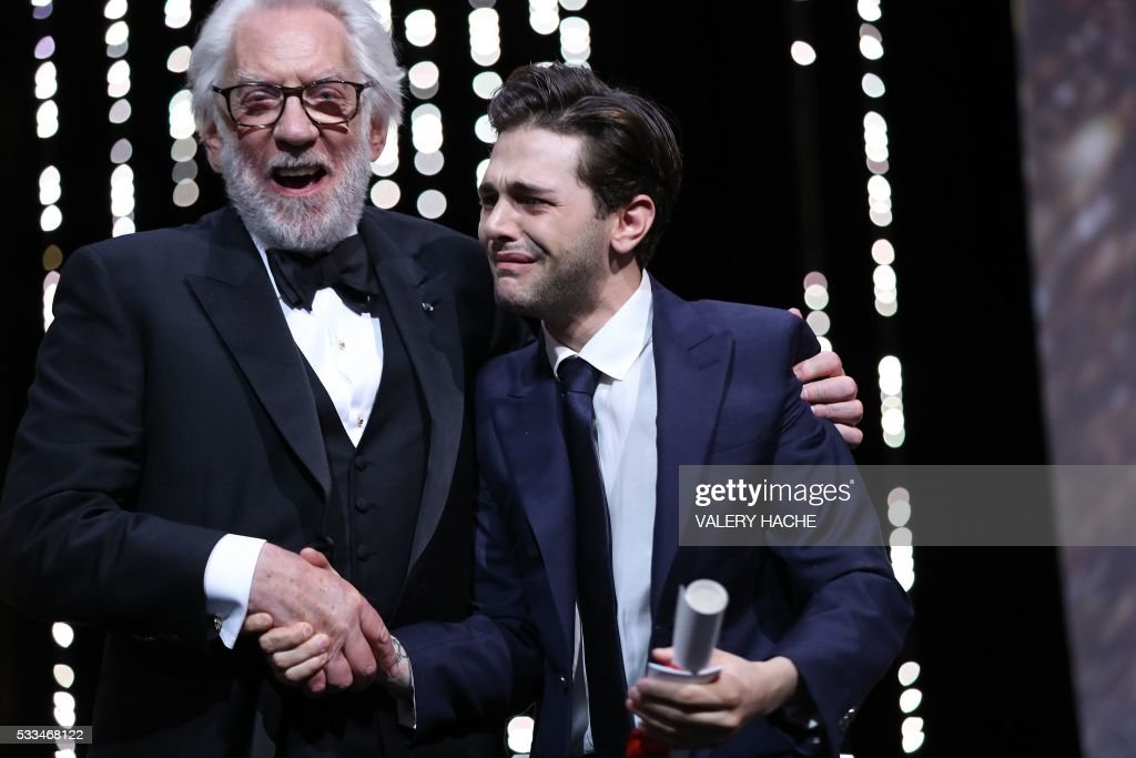 TOPSHOT - Canadian director Xavier Dolan (R) is congratulated on stage by Canadian actor and member of the Jury Donald Sutherland after being awarded with the Grand Prix for the film 'It's Only The End Of The World (Juste La Fin Du Monde)' during the closing ceremony of the 69th Cannes Film Festival in Cannes, southern France, on May 22, 2016. / AFP PHOTO / Valery HACHE