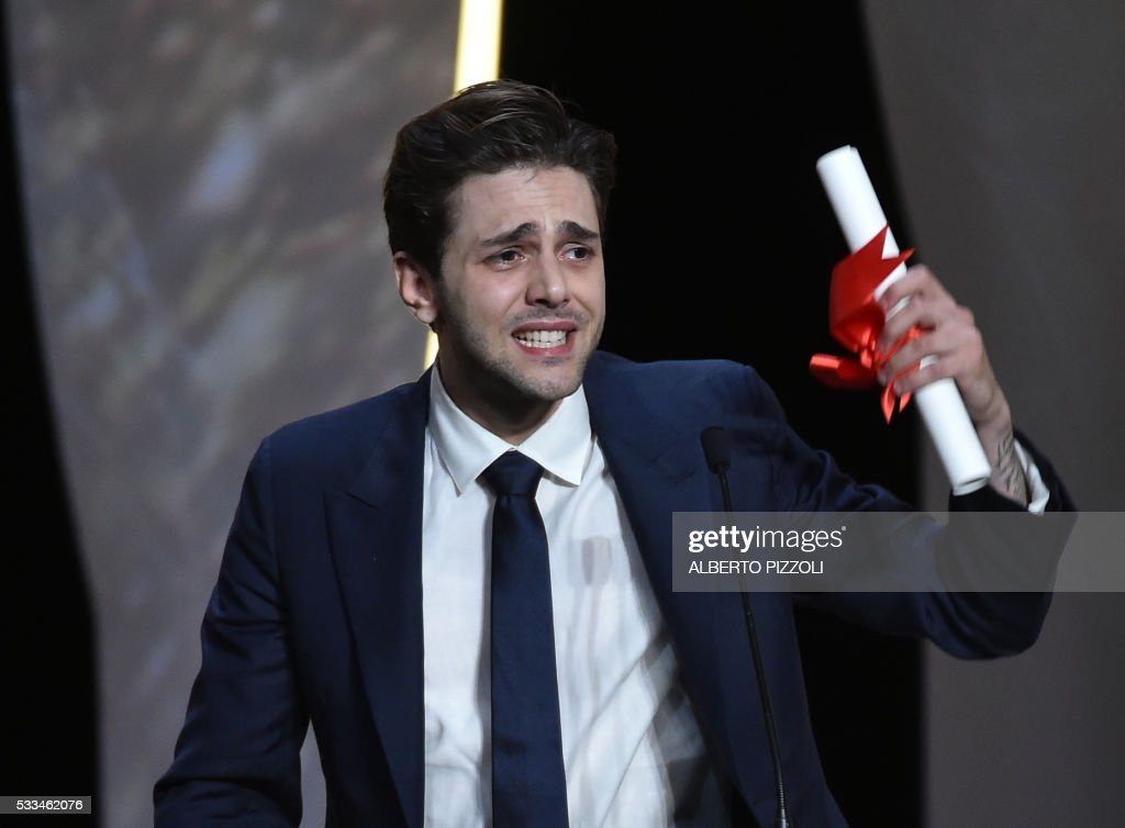 TOPSHOT - Canadian director Xavier Dolan reacts on stage after being awarded with the Grand Prix for the film 'It's Only The End Of The World (Juste La Fin Du Monde)' during the closing ceremony of the 69th Cannes Film Festival in Cannes, southern France, on May 22, 2016. /