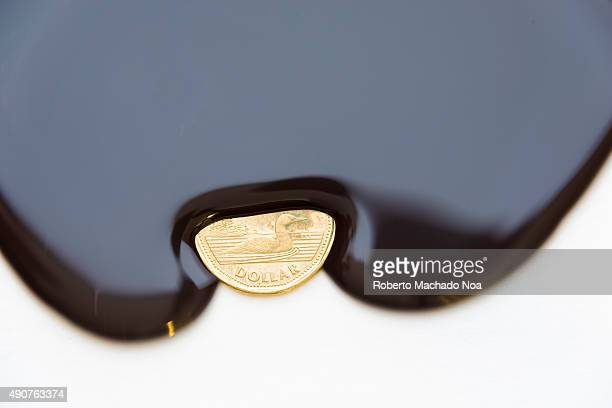 Canadian dollar a petro dollar currency Thick black liquid engulfing a coin from three sides A one dollar Canadian coin is half covered by a dense...