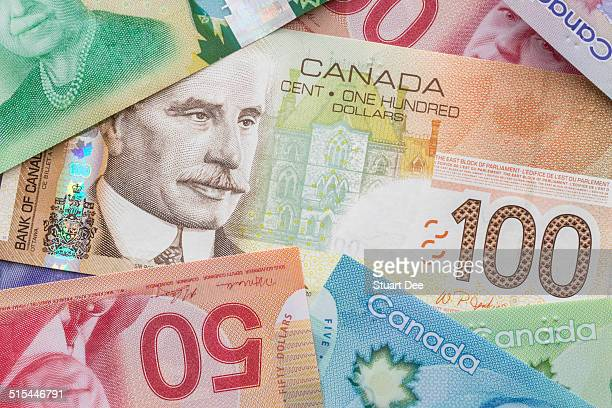 canadian dollar bills - canadian one hundred dollar bill stock pictures, royalty-free photos & images