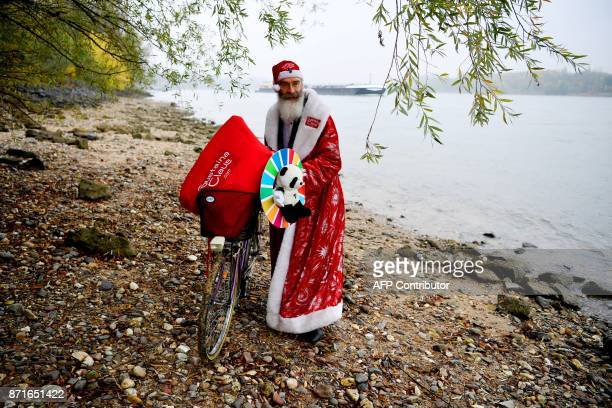 Canadian environmentalist Philip McMaster dressed up as Santa Claus poses on the shore of the Rhine river on November 8 2017 in Bonn where he attends...