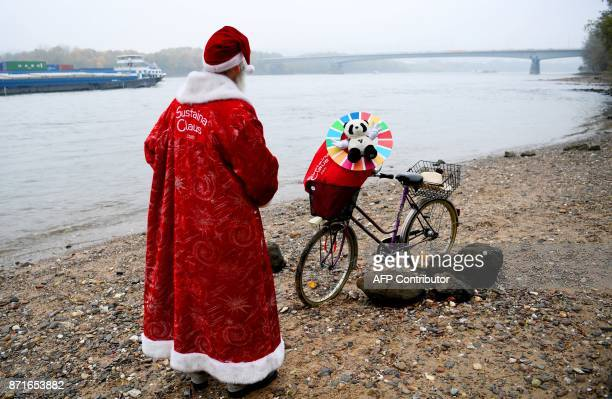 Canadian environmentalist Philip McMaster dressed up as Santa Claus stands next to his bicycle on the shore of the Rhine river on November 8 2017 in...