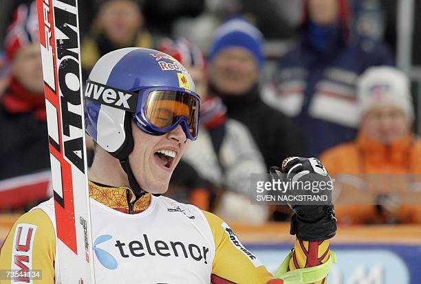 Canadian Erik Guay celebrates a second place behind Swiss Didier Cuche and ahead of third placed Marco Buechel of Liechtenstein in the WC Downhill...